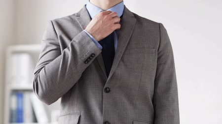 üzleti öltöny : people business fashion and clothing concept  close up of man in suit adjusting necktie at office