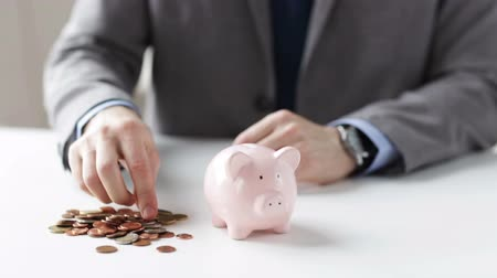 bank : people money saving investing finances concept  close up of businessman putting coins into piggy bank