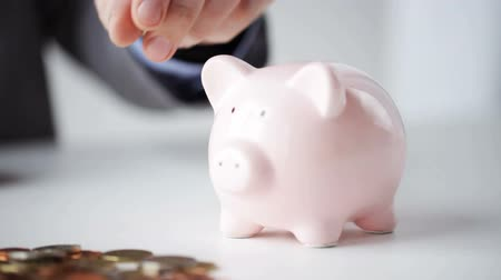 банк : people money saving investing finances concept  close up of businessman putting coins into piggy bank