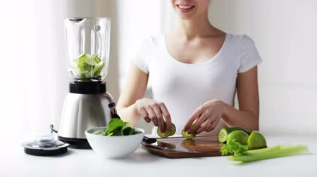 sağlıklı beslenme : healthy eating cooking vegetarian food dieting and people concept  smiling young woman with blender and green vegetables for detox shake or smoothie at home