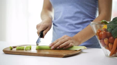 sağlıklı beslenme : healthy eating vegetarian food cooking  dieting and people concept  close up of young woman chopping celery at home