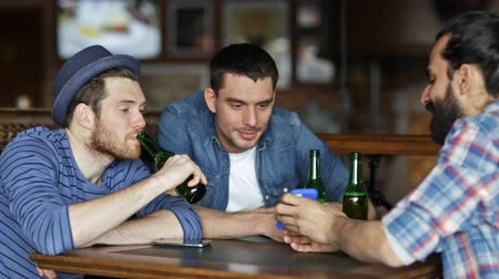 bebida alcoólica : people men leisure friendship and technology concept  happy male friends with smartphones drinking bottle beer at bar or pub
