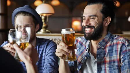 pint glass : people toast leisure friendship and celebration concept  happy male friends drinking beer and clinking glasses at bar or pub