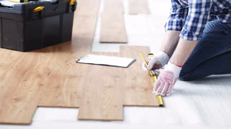 лента : repair building floor and people concept  close up of man measuring flooring with ruler and writing to clipboard Стоковые видеозаписи
