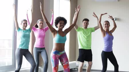 sınıf : fitness sport dance and lifestyle concept  group of smiling people with coach dancing zumba in gym or studio Stok Video
