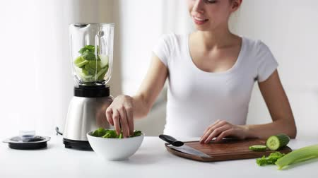 confecção : healthy eating, cooking, vegetarian food, dieting and people concept - smiling young woman with blender and green vegetables making detox shake or smoothie at home
