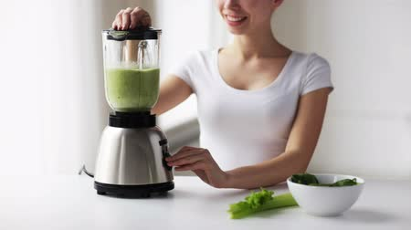 sağlıklı beslenme : healthy eating, cooking, vegetarian food, dieting and people concept - smiling young woman with blender and green vegetables making detox shake or smoothie at home