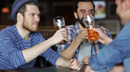 pint glass : people, men, leisure, friendship and celebration concept - happy male friends drinking beer and clinking glasses at bar or pub
