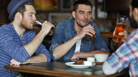 паб : people, leisure, friendship and celebration concept - happy male friends drinking beer, eating snacks and clinking glasses at bar or pub Стоковые видеозаписи