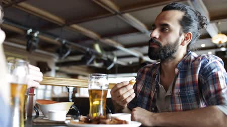 sarımsak : people, men, leisure, friendship and communication concept - happy male friends drinking beer and eating bread snack a at bar or pub