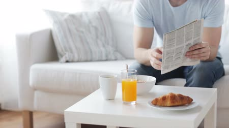 gevreği : leisure, breakfast and people concept - close up of man reading newspaper and drinking coffee at home