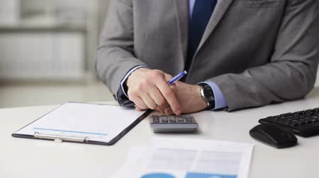 business, finances, people, technology and office work concept - close up of businessman with papers and calculator Stock Footage