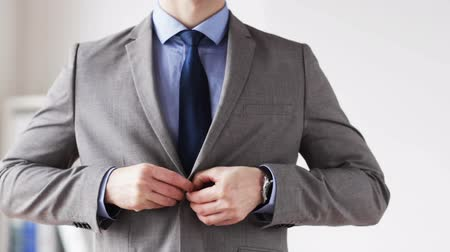 krawat : people, business, fashion and formal wear concept - close up of businessman in suit fastening button on jacket and adjusting necktie at office Wideo