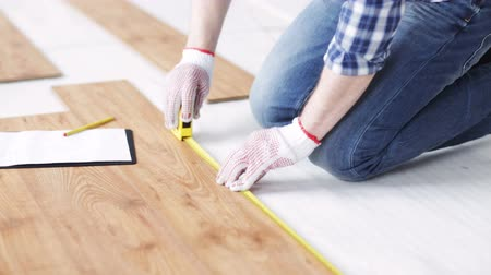 паркет : repair, building, floor and people concept - close up of man measuring flooring with ruler and writing to clipboard