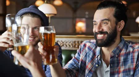 na zdraví : people, toast, leisure, friendship and celebration concept - happy male friends drinking beer and clinking glasses at bar or pub Dostupné videozáznamy