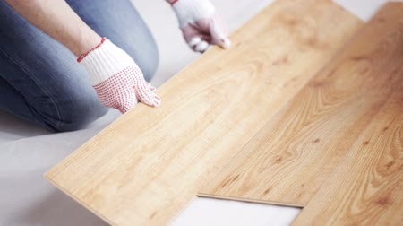 паркет : repair, building, floor and people concept - close up of man installing wood flooring