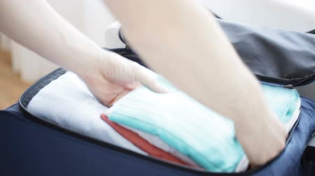zsák : trip, travel, vacation, luggage and people concept - close up of male hands packing clothes into travel bag at home