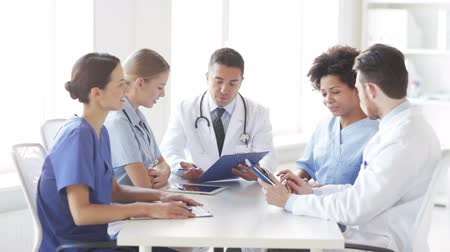 Латиноамериканское : hospital, profession, people and medicine concept - group of happy doctors with clipboard meeting and discussing something at medical office Стоковые видеозаписи