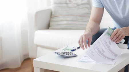 loans : finances, business, economy and people concept - close up of man with calculator and bills counting money at home