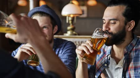 bebida alcoólica : people, toast, leisure, friendship and celebration concept - happy male friends drinking beer and clinking glasses at bar or pub Stock Footage