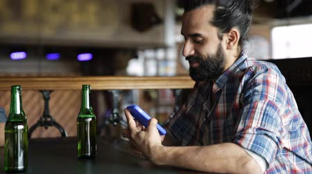broda : people, leisure, and technology concept - happy man with beard drinking bottle beer and showing his smartphone to someone at bar or pub