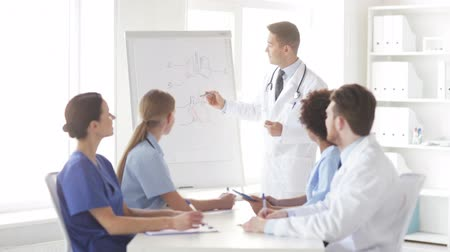 zdravotní : hospital, profession, medical education, people and medicine concept - group of happy doctors meeting at presentation or interns with mentor showing human organs drawings on flip board in hospital Dostupné videozáznamy