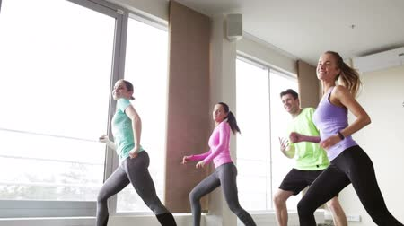 koç : fitness, sport, dance and lifestyle concept - group of smiling people with coach dancing zumba in gym or studio
