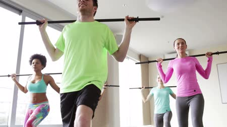 equipamentos esportivos : fitness, sport, training, gym and lifestyle concept - group of people exercising with bars in gym