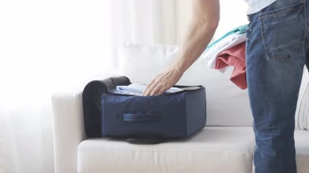 bagagem : trip, travel, vacation, luggage and people concept - close up of man packing clothes into travel bag at home