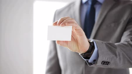 blank : business, people, education, office and advertising concept - close up of businessman in suit showing white blank visiting card Stock Footage