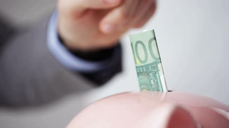 банк : people, financial savings, investing and economy concept - close up of businessman putting paper money into piggy bank