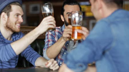 паб : people, men, leisure, friendship and celebration concept - happy male friends drinking beer and clinking glasses at bar or pub