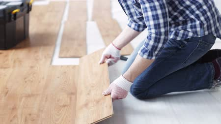 устанавливать : repair, building, floor and people concept - close up of man installing wood flooring