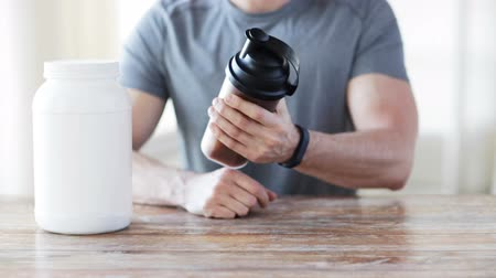 сотрясение : sport, fitness, healthy lifestyle and people concept - close up of man in fitness bracelet with jar and bottle preparing protein shake