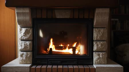 helyek : heating, warmth, fire and cosiness concept - close up of burning fireplace at home