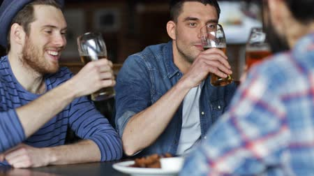 na zdraví : people, men, leisure, friendship and celebration concept - happy male friends drinking beer and clinking glasses at bar or pub