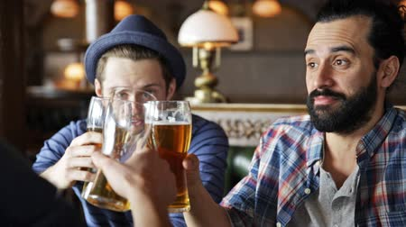 comemoração : people, toast, leisure, friendship and celebration concept - happy male friends drinking beer and clinking glasses at bar or pub Vídeos