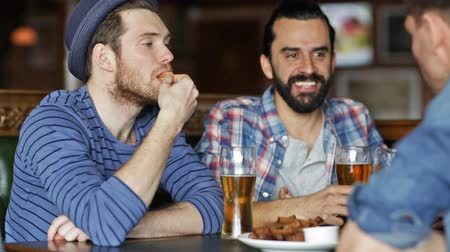 паб : people, men, leisure, friendship and communication concept - happy male friends drinking beer and eating bread snack a at bar or pub