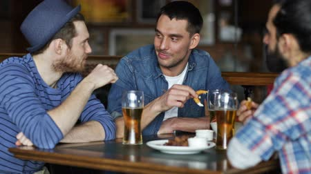 bebida alcoólica : people, men, leisure, friendship and communication concept - happy male friends drinking beer and eating tasty snacks a at bar or pub Stock Footage