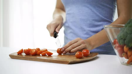 разделочная доска : healthy eating, vegetarian food, cooking, dieting and people concept - smiling young woman chopping cherry tomatoes at home