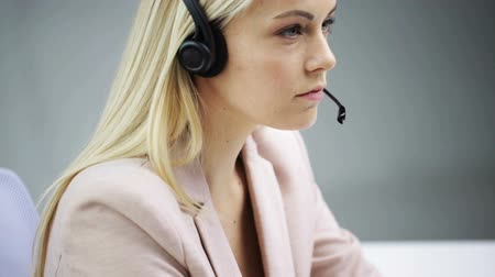 aggódó : business, people, communication and technology concept - businesswoman with computer and headset talking Stock mozgókép