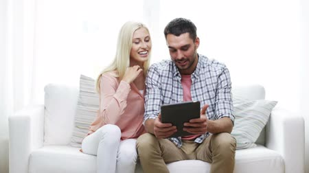 galeria : love, family, technology, internet and happiness concept - smiling happy couple with tablet pc computer browsing photo gallery preview at home Stock Footage