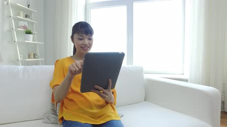 гостиная : people, technology and leisure concept - happy young asian woman sitting on sofa with tablet pc computer at home