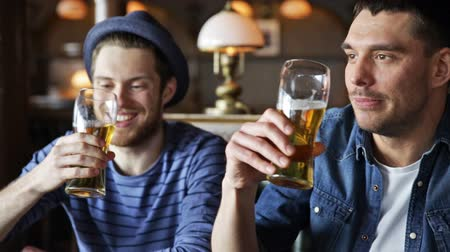 детеныш : people, toast, leisure, friendship and celebration concept - happy male friends drinking beer and clinking glasses at bar or pub Стоковые видеозаписи