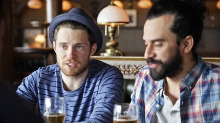 pint glass : people, leisure, friendship and celebration concept - happy male friends drinking beer, eating snacks and clinking glasses at bar or pub Stock Footage