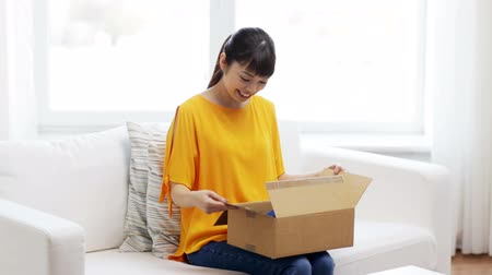shipping : people, delivery, commerce, shipping and shopping concept - happy asian young woman taking jeans out of cardboard parcel box at home