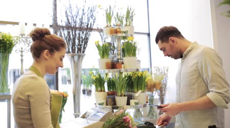 karta kredytowa : people, shopping, sale, floristry and consumerism concept - happy florist woman counting bunch cost at cashbox and man with credit card paying for purchase at flower shop Wideo