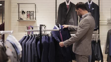 clothing : sale, shopping, fashion, style and people concept - elegant young man in suit choosing clothes in mall or clothing store