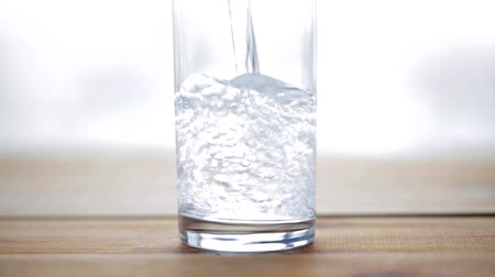 doldurmak : healthy eating, diet and drinks concept - water pouring into glass on wooden table