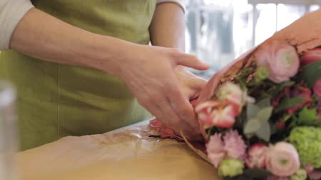 floral composition : people, shopping, sale, floristry and consumerism concept - florist man wrapping flowers in paper at flower shop Stock Footage